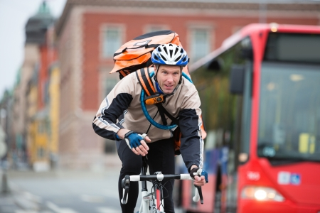 messenger: Male Cyclist With Courier Delivery Bag Riding Bicycle