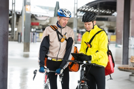 Courier Delivery Men With Bicycles Using Digital Tablet Stock Photo - 16672693