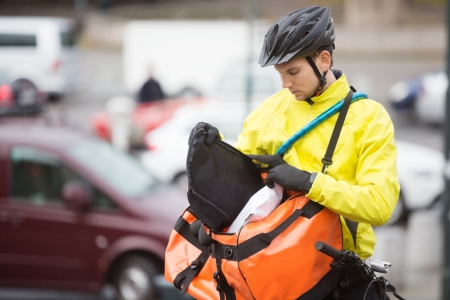 Young Male Cyclist Putting Package In Courier Bag photo