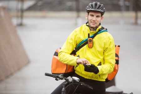 Male Cyclist With Courier Bag Using Mobile Phone On Street Stock Photo - 16672698