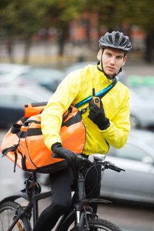 Male Cyclist With Courier Bag Using Walkie-Talkie On Street Stock Photo - 16672696