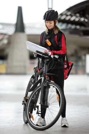 Female Cyclist With Courier Bag And Package On Street photo