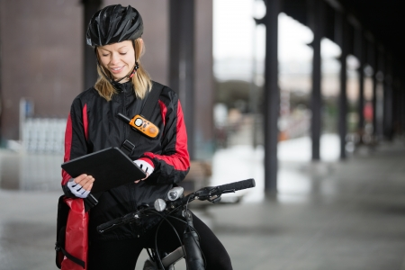 Female Cyclist With Courier Bag Using Digital Tablet photo