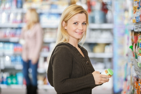 Smiling Young Woman Shopping At Supermarket photo