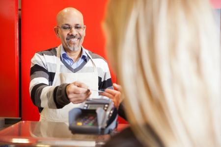 oficinista: Hombre maduro aceptar tarjetas de crédito de la mujer joven en el supermercado