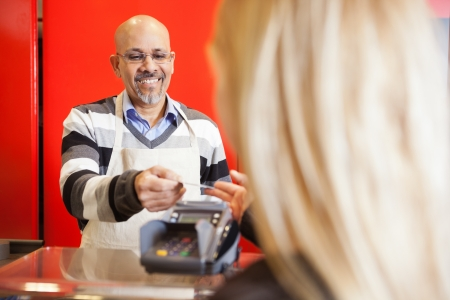 accepting: Mature Man Accepting Credit Card From Young Woman At Supermarket Stock Photo
