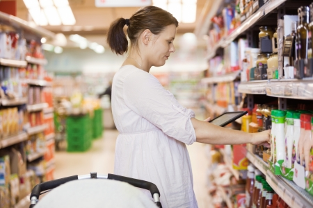shopping carriage: Mid Adult Woman Using Digital Tablet At Supermarket Stock Photo
