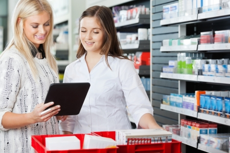 pharmacist: Woman With Friend Using Digital Tablet At Supermarket