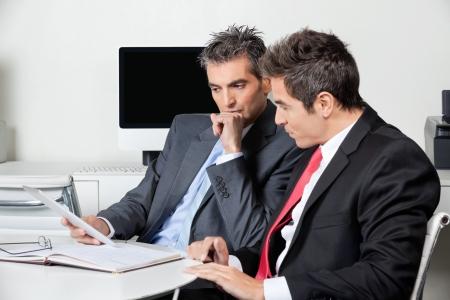 ejecutivos: Hombres de negocios pensativo que usa la tableta Digital En El Escritorio