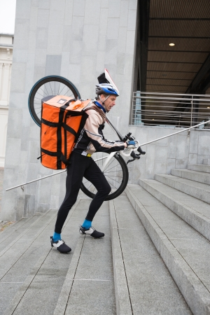 Male Cyclist With Courier Bag And Bicycle Walking Up Steps photo