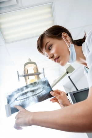 hygienist: Female Dentist Looking At X-Ray Image