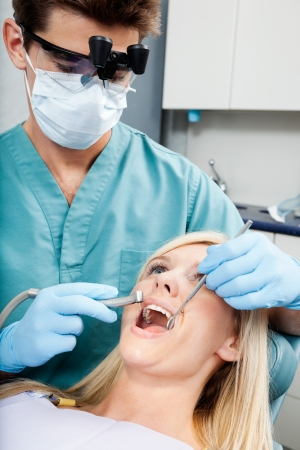 Dentist Treating A Female Patient At Clinic photo