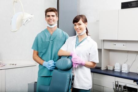 Dos dentistas sonrientes junto a la silla dental en cl�nica photo