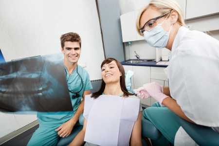 Dentist With Female Assistant Showing X-Ray Image To Patient Stock Photo - 16715252