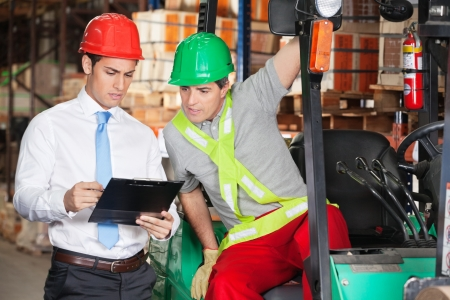forklift driver: Supervisor Showing Clipboard To Forklift Driver Stock Photo