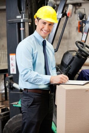 Young Supervisor Writing On Clipboard At Warehouse photo