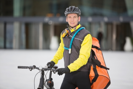 Young Male Cyclist With Courier Delivery Bag photo