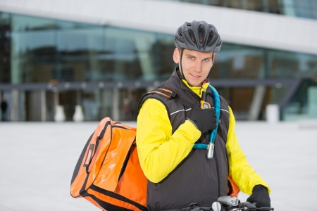 Cyclist With Courier Delivery Bag Using Walkie- Talkie photo