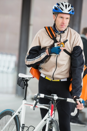 Male Cyclist With Courier Bag Using Walkie-Talkie photo