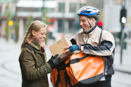 Young Woman Receiving A Package From Courier Delivery Man Stock Photo - 16715234