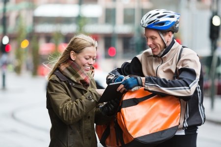 Courier Delivery Man Showing Digital Tablet To Young Woman Stock Photo - 16715235