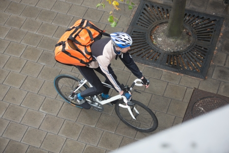 Male Cyclist With Backpack On Sidewalk photo