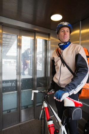 Male Cyclist With Courier Bag Riding In An Elevator photo