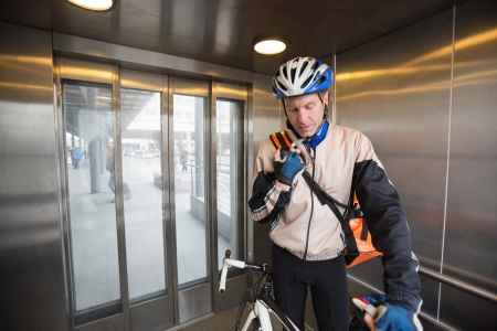 Male Cyclist With Courier Bag In An Elevator photo