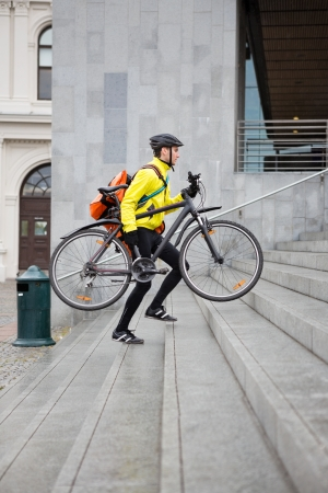 Courier Delivery Man With Bicycle And Backpack Walking Up Steps Stock Photo - 16715228