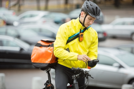 Male Cyclist With Courier Bag Using Mobile Phone On Street photo