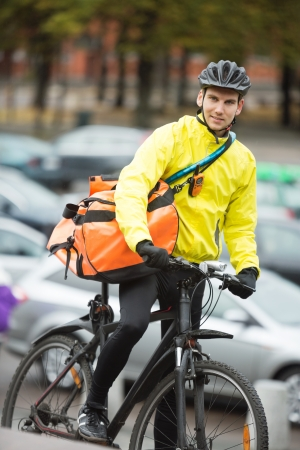 Male Cyclist With Courier Delivery Bag On Street photo