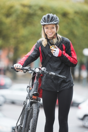 Female Cyclist With Courier Bag Using Walkie-Talkie Stock Photo - 16715227