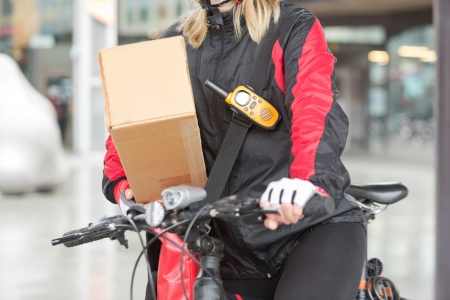 Female Cyclist With Cardboard Box And Courier Bag On Street Stock Photo - 16715217