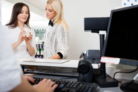 drug store: Sales Clerk Assisting Woman In Pharmacy Stock Photo