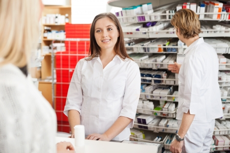 customer assistant: Female Pharmacist Helping Customer Stock Photo