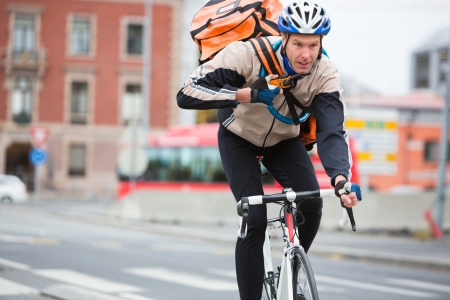 Male Cyclist With Courier Delivery Bag Riding Bicycle photo