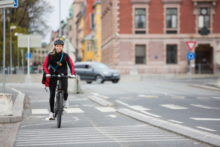 Female Cyclist With Courier Delivery Bag On Street photo