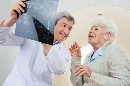 Doctor With Patient Looking At X-ray photo