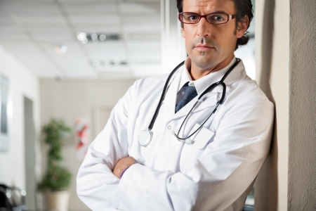 serious doctor: Doctor Standing With Hands Folded Stock Photo