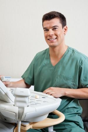 medical examination: Male Technician Operating Ultrasound Machine