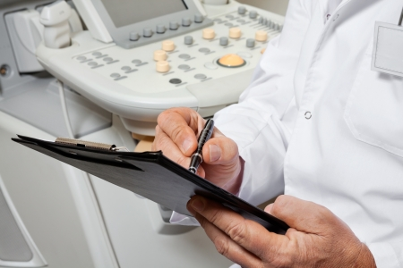 radiologist: Male Doctor Writing On Clipboard