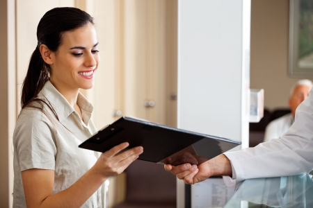 Receptionist Taking Clipboard From Doctor photo