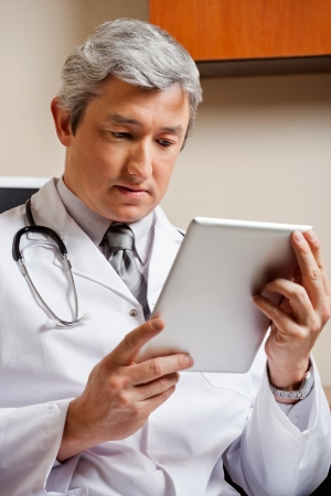 Doctor Looking At Digital Tablet photo