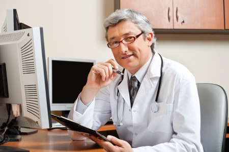 Doctor Sitting At Desk In Front Of Computer Stock Photo - 17100159