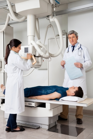 Radiologists With Patient In X-ray Room Stock Photo - 17100203