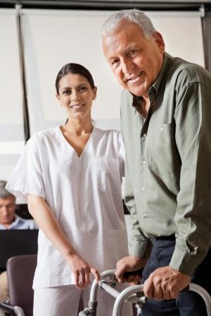 marcheur: Infirmi�re Aider les patients M�le Avec Walker Banque d'images