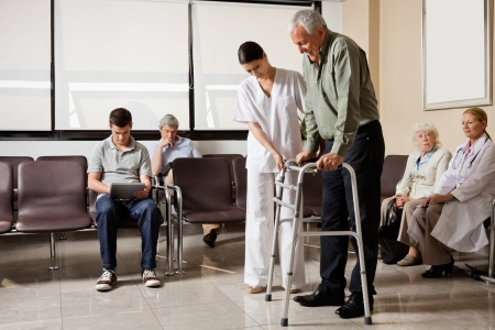 Man Being Helped By Nurse To Walk Zimmer Frame photo