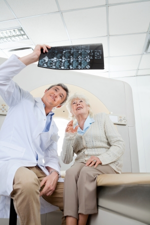 Radiologist With Patient Looking At X-ray photo