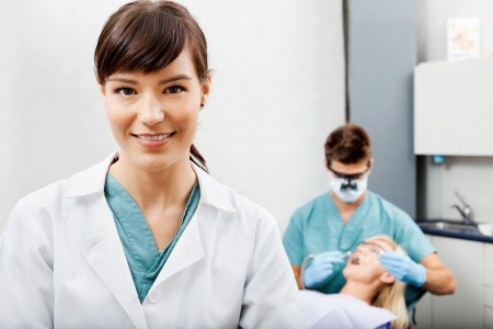 dentist mask: Female Assistant With Dentist Working In The Background Stock Photo