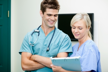 Young Female Nurse Showing Clipboard To Male Vet Stock Photo - 17132830